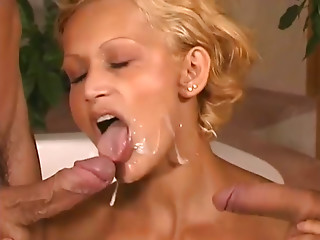 Blonde Corry May takes cumshots on her face standing on her knees