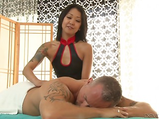Tattooed Asian masseur provides her customer with a fine dick ride