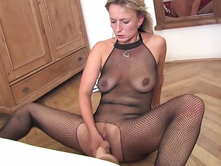 Solo model in fishnet pantyhose sits her twat against a huge dildo in her lonely apartment