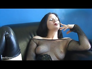 Sexy woman smokes on black sofa in hot style