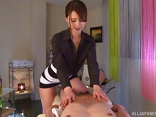 Japanese woman uses oil while massaging a man's cock