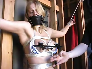 Tied to the wall, this slave gets clamps put on her nipples